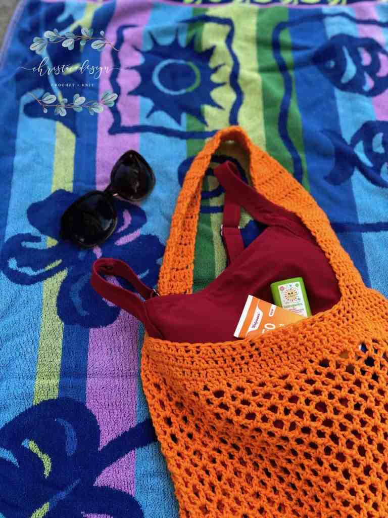 picture of orange crochet market tote bag on beach towel