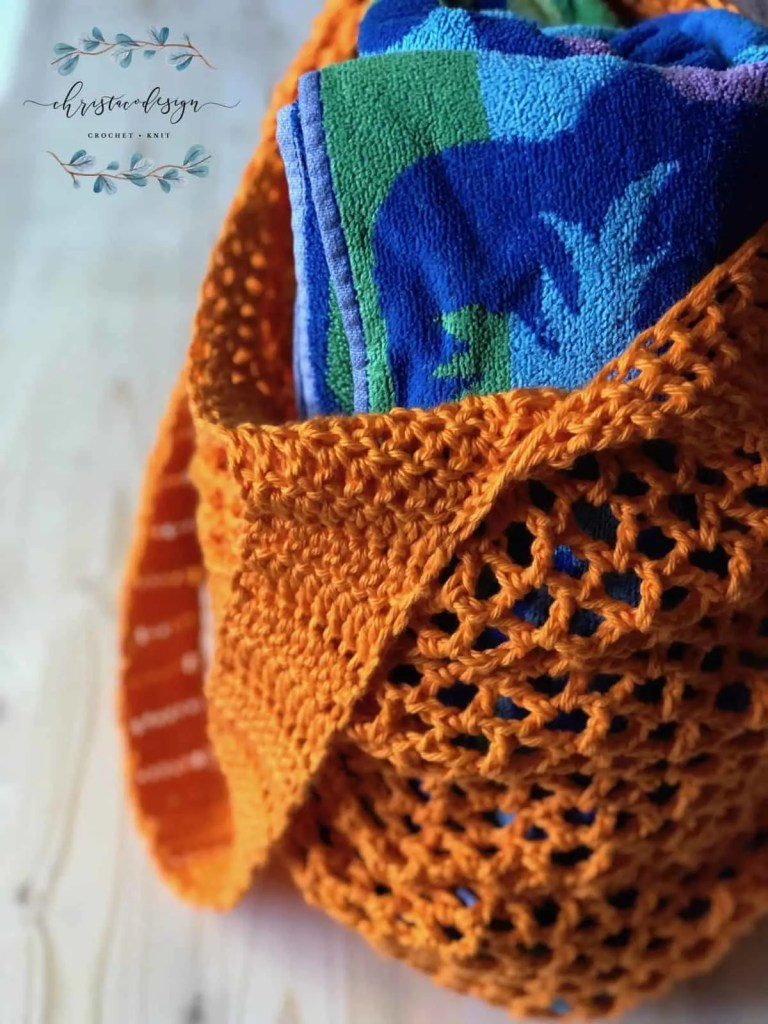 picture of orange crochet market tote bag full of blue beach towel