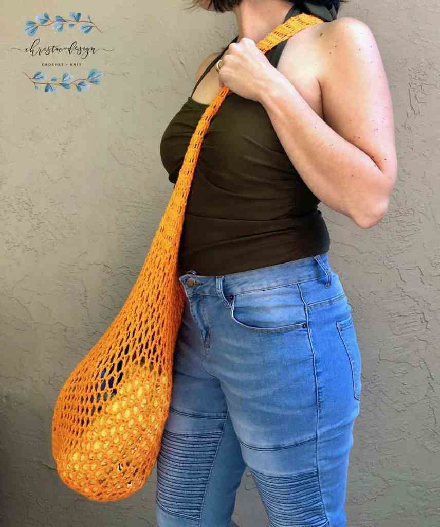 picture of woman with crossbody strap of orange market tote bag
