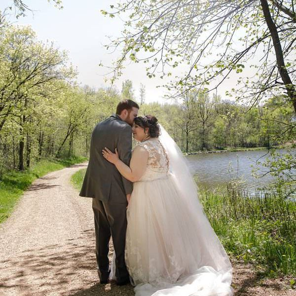 couple at the edge of a gravel path by a lake at oak ridge in chaska before their wedding