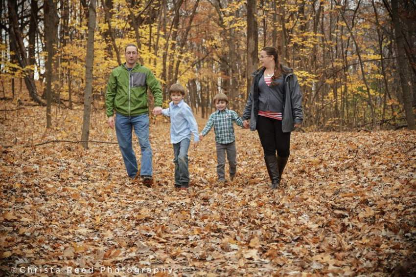 family holds hands and walks in woods for lake ann park portraits