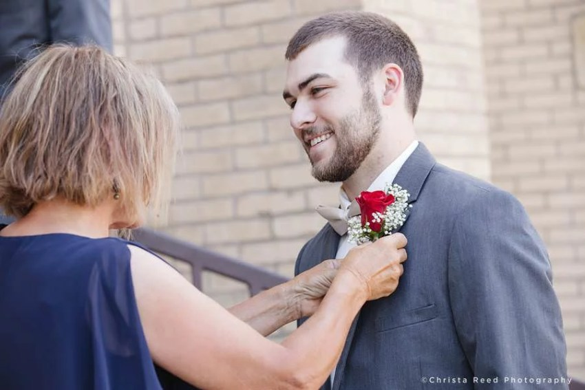 in Mankato the groom's mother fastens on his rose boutonnière
