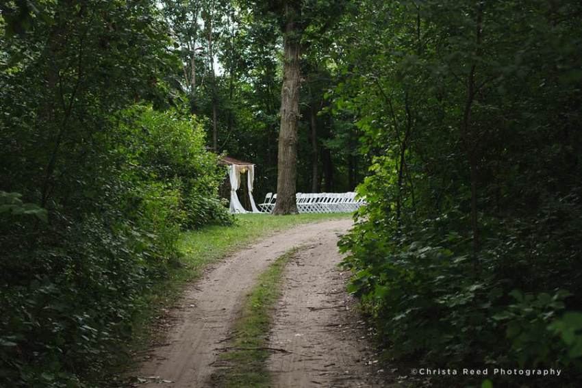 wooded dirt road leading to outdoor wedding ceremony