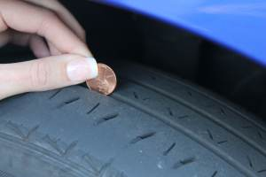A penny inserted into a tire tread