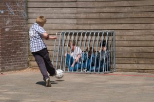 Bully torments victims in cage with soccer ball.