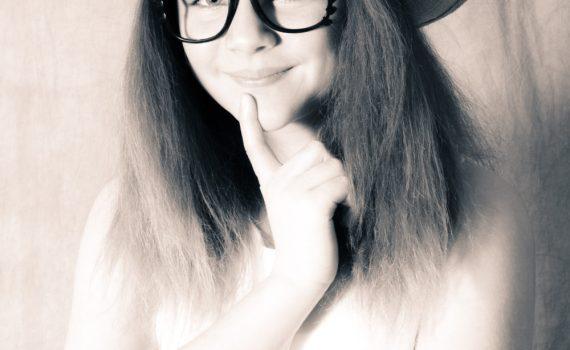 Amina med glasögon och hatt