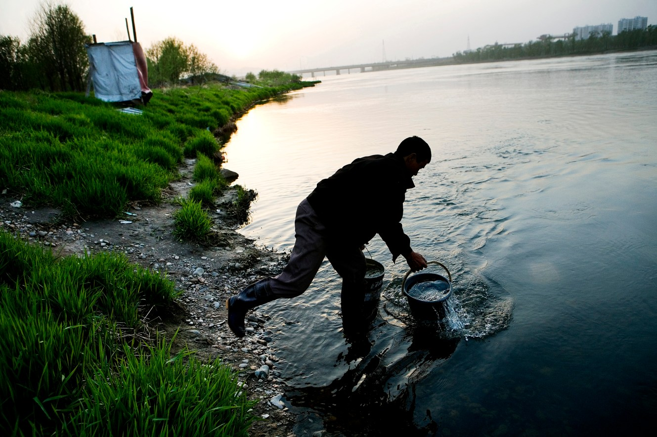 Shang Maoping fetch water directly from the river like millions of other people residing along Songhua River. The little tarped woodwork behind Shang is his familyÕs only lavatory. Songhua is the main water source for more than 62 million people in Northeast China. Christian Als / GraziaNeri