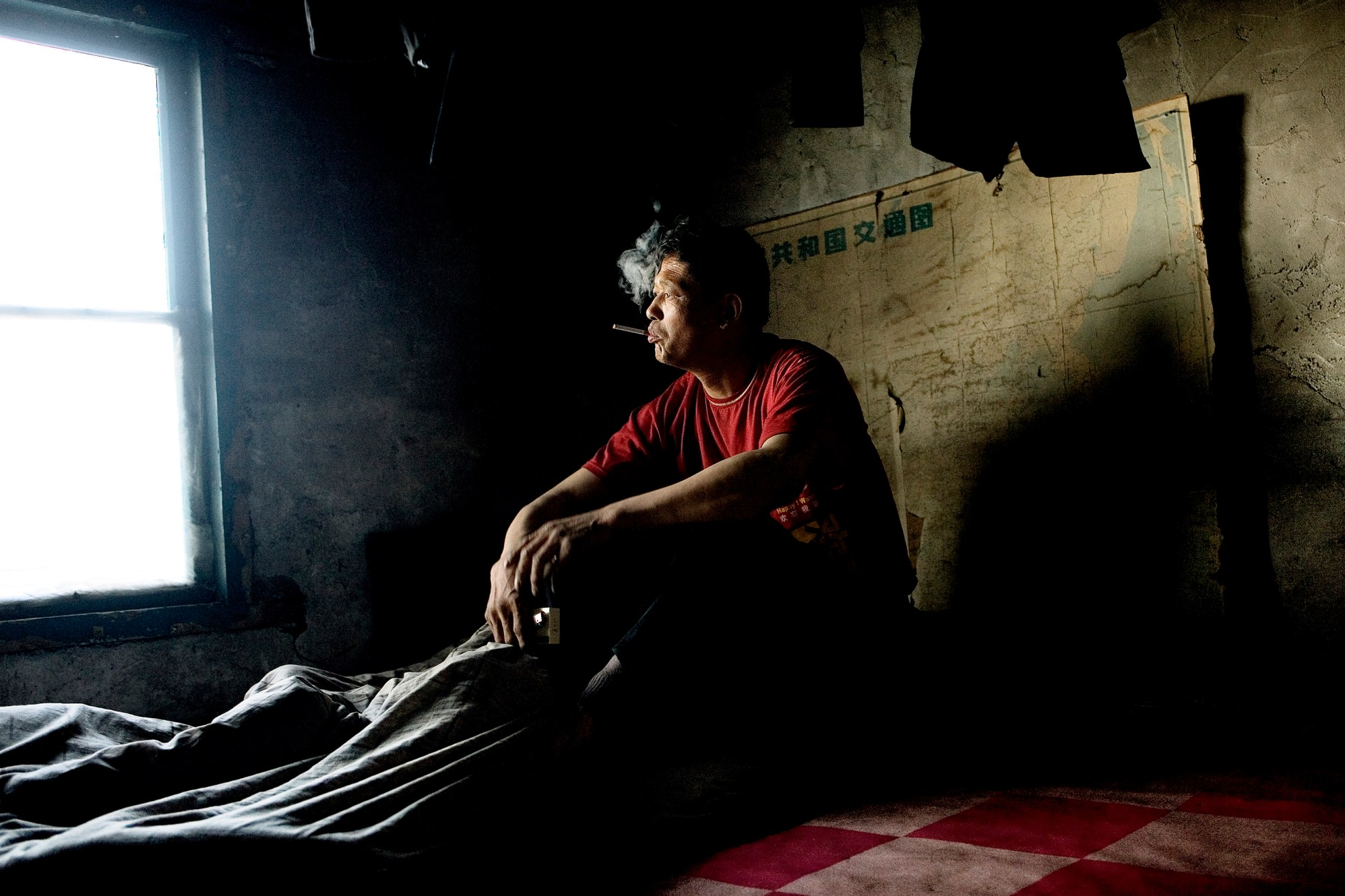 The first cigarette of the day quickly fills the room, seconds after the oldest brother of the migrant family, Jiang Jigao, has awoken early in the morning. Soon after the 14 hour-a-day work at the paper factory run-outs begins. He used to work as a fisherman, but there are no longer any fish in the river that runs through his village. Christian Als / GraziaNeri