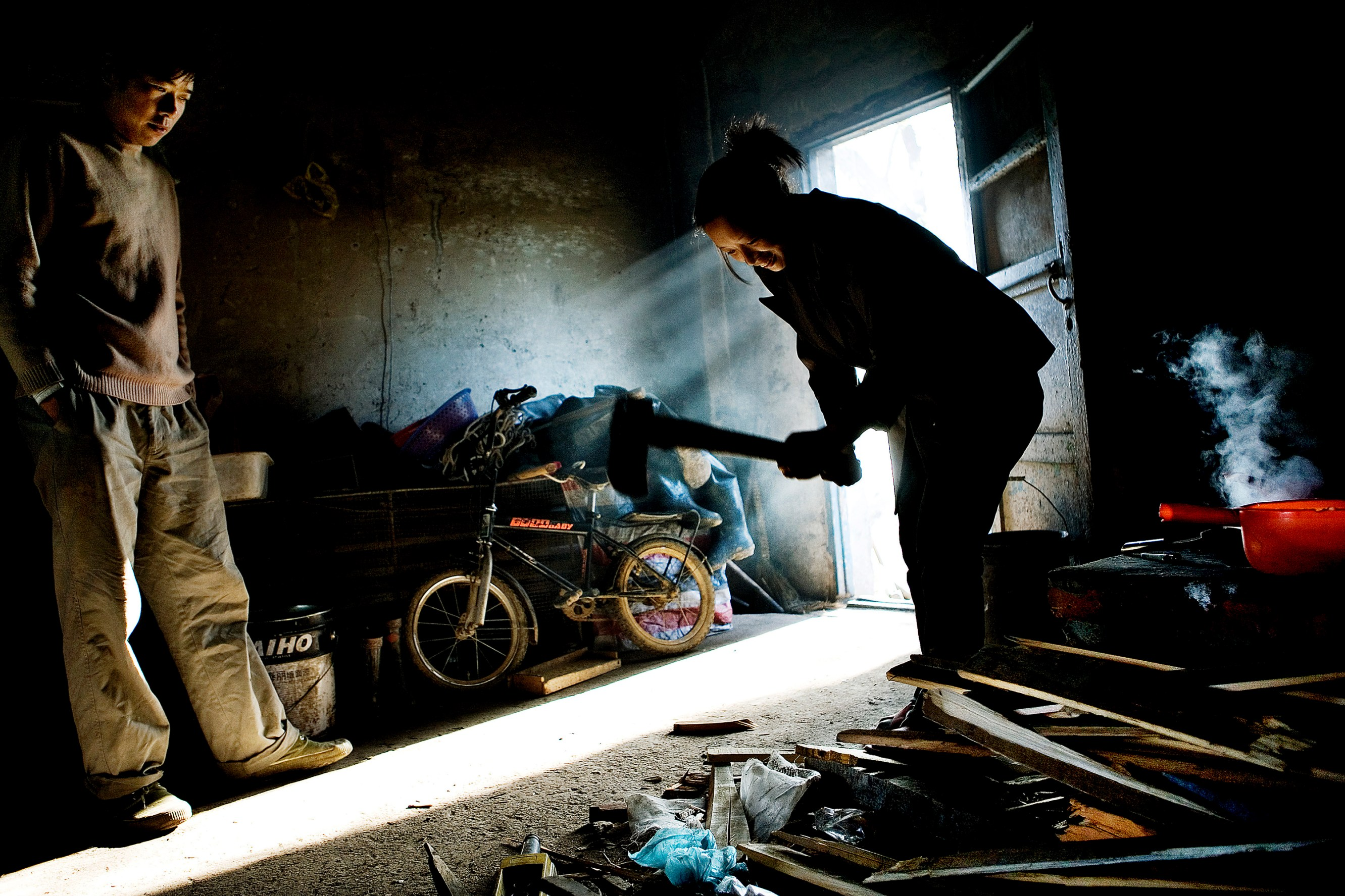 The family has to boil up water in the morning to wash the sleep away from their eyes, so Yang Chaozhen is cutting up wood for the open fireplace, before the day's work at the sewage lines begins. Christian Als / GraziaNeri