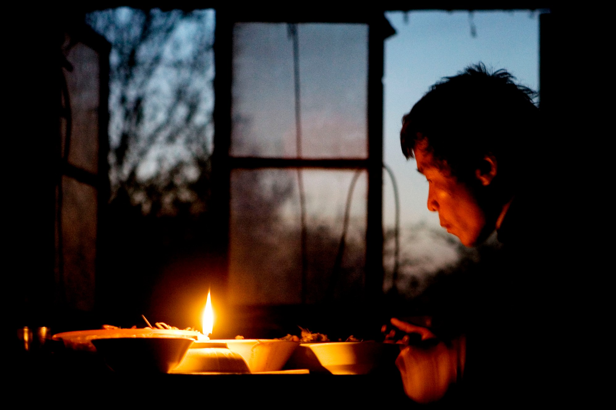 There's no electricity in the house, so Jiang Jichao eats in the light of a candle. In the background you can hear a small radio playing traditional, Chinese music.