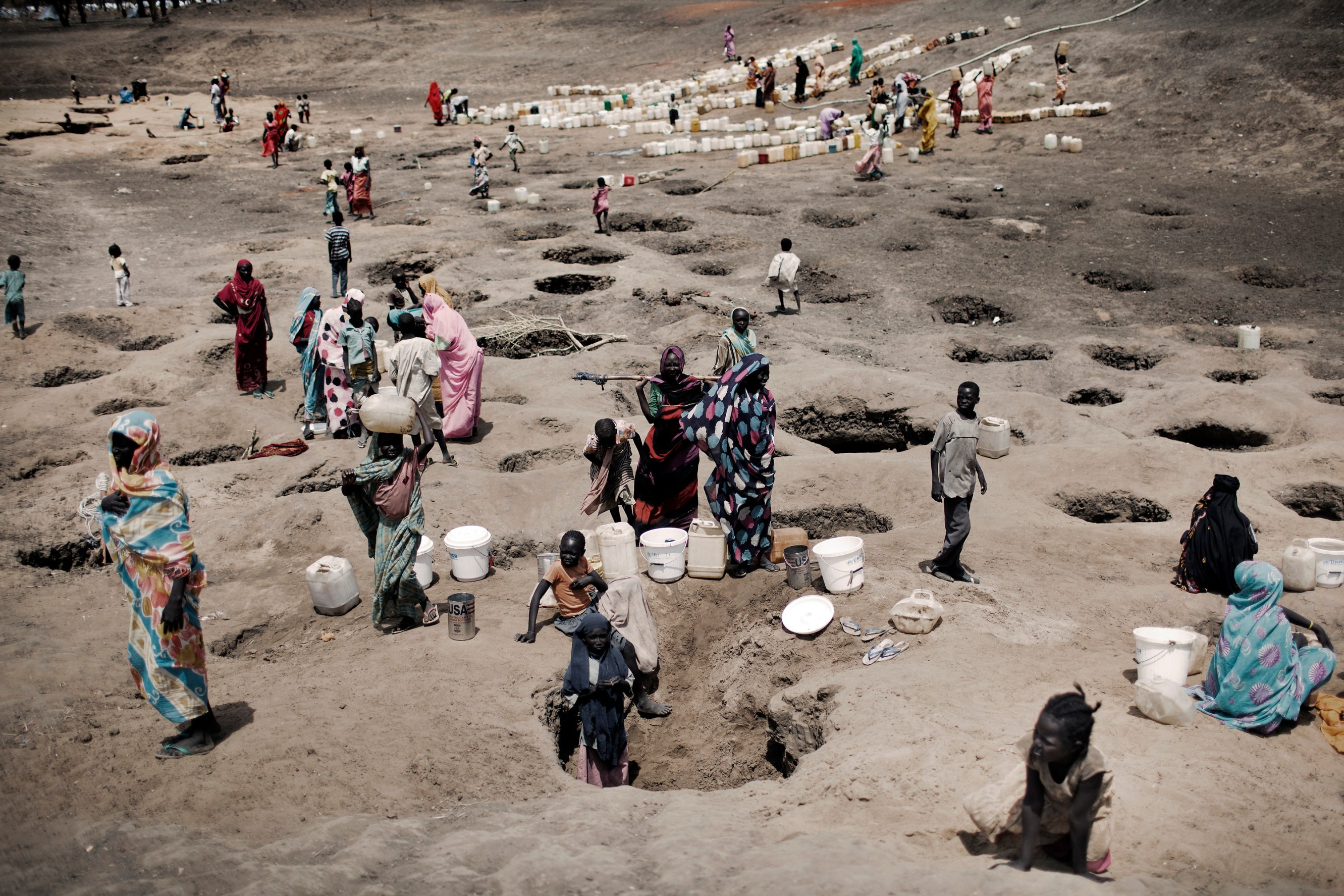 People collect water from various wells dug by refugees in Jammam camp. With waiting times at official camp water stations of up to six hours, camp dwellers have started to dig for new water sources.