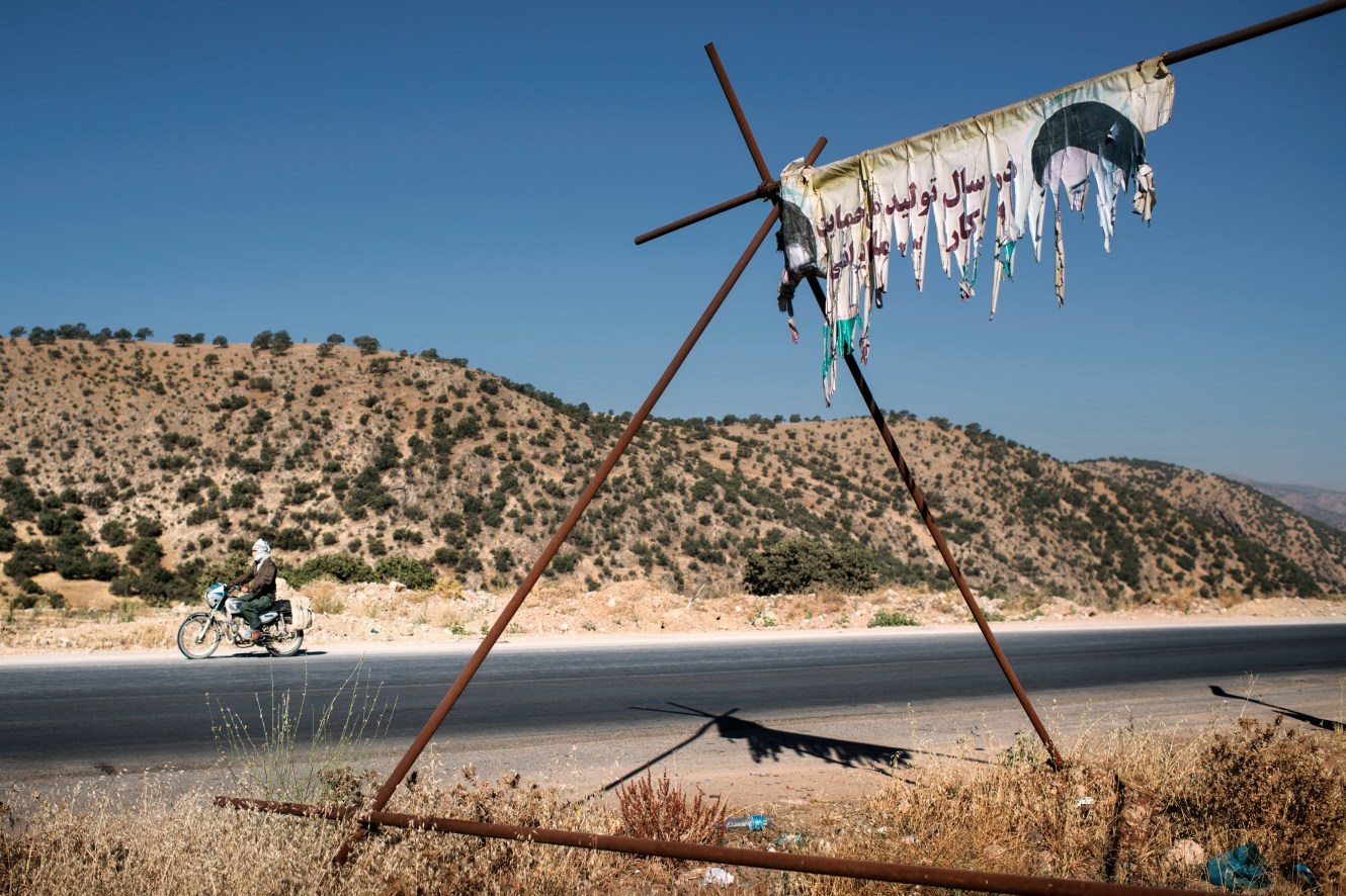 A tattered poster displaying the ever present image of Ayatollah Khomeini on a mountain road in the Zagros Mountains, near Shiraz.