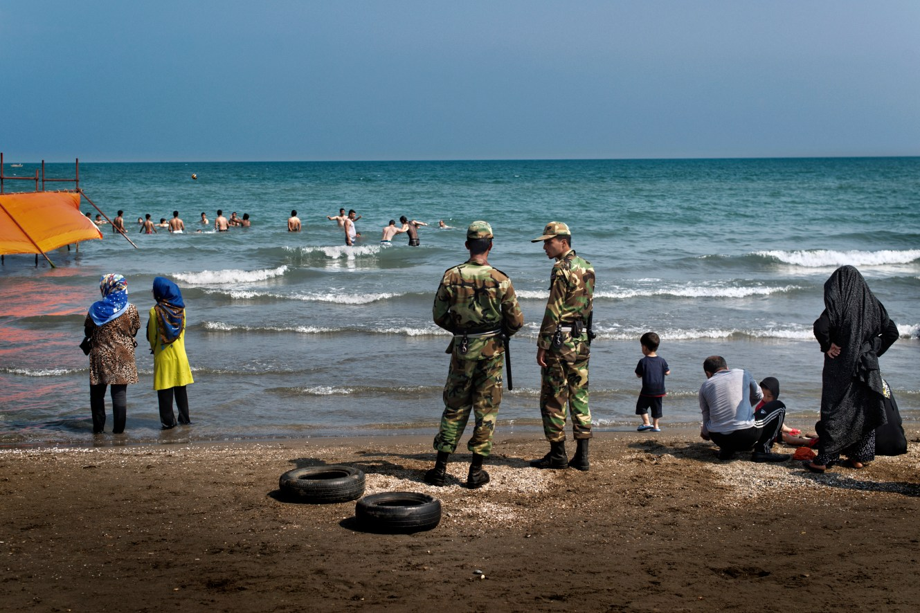 Police officers patrols the beach at the Caspian Sea beach of Sisangan, near Nour. Women are not allowed to swim, and men only in designated areas surrounded by orange plastic tarps.