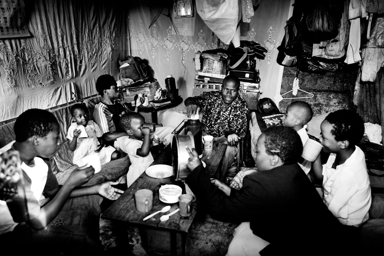 The Odongo Family eating breakfast in the house. Clockwise from left it is Lavenda, Naomi, Meshak, Michelle, Augustin Odongo, Cynthia, Eunice and Clarissa. Homes in Kibera are made out of corrugated tin, mud, cardboard and plastic and consist of one room that serves as a kitchen, living room, and bedroom. Most homes are about 3 meters by 3 meters and have an average of five people living in them.