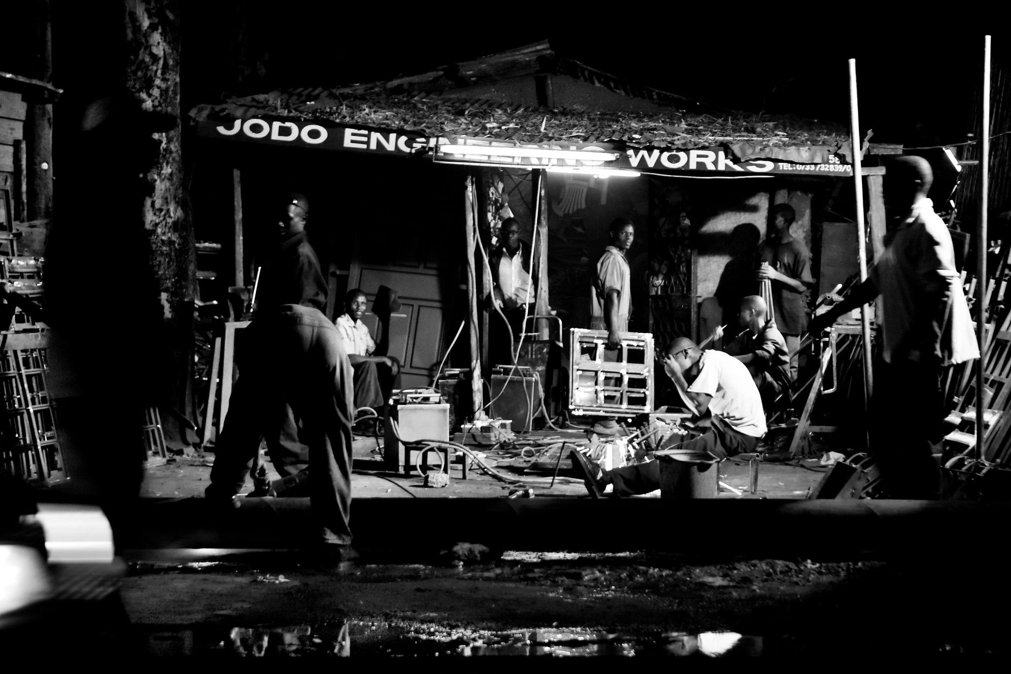 Young men works the late night shift in a car repairs shop. Most shops in Kibera stays open until midnight.