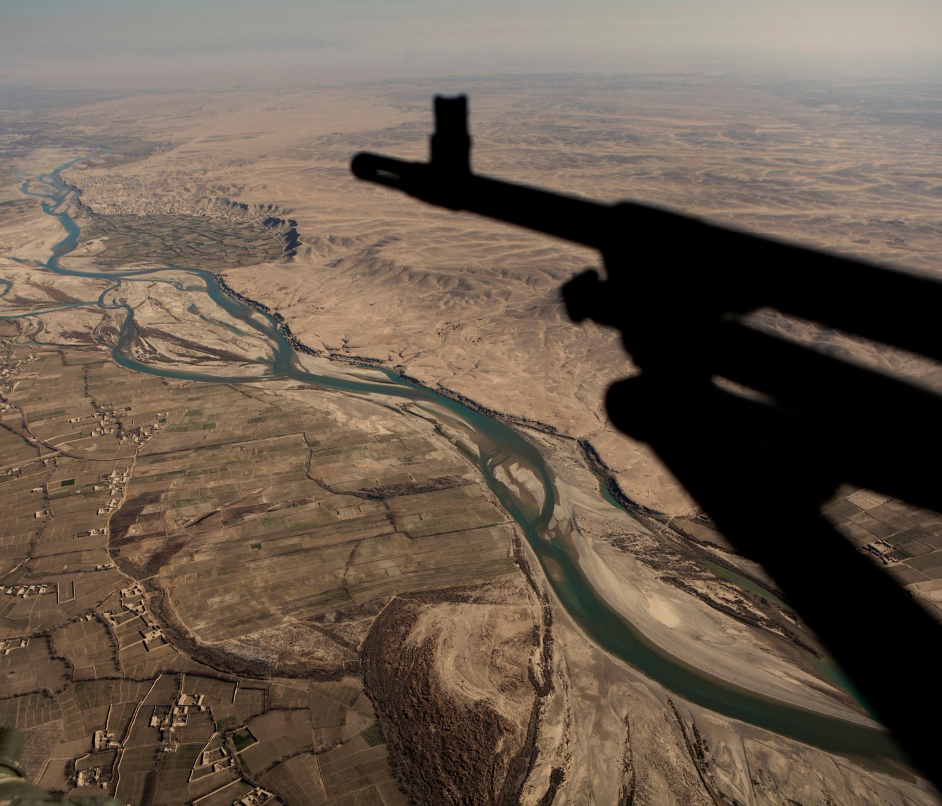 The gunners view from a Danish military helicopter as it flies over the Helmand River. In June 2011, President Obama announced his plan to begin the withdrawal of US troops from Afghanistan, but there is currently no end date for the war in the troubled country. Helmand is the largest province in Afghanistan, and the heart of the war against terror. Commanders on the ground have described the situation as the most brutal conflict the British Army has been involved in since the Korean War. Much of the fighting between NATO and Taliban forces is taking place in this province and Helmand is a true Taliban stronghold. The Helmand River flows through the mainly desert region. With these images I am trying to show a softer side to this troubled area of Afghanistan.