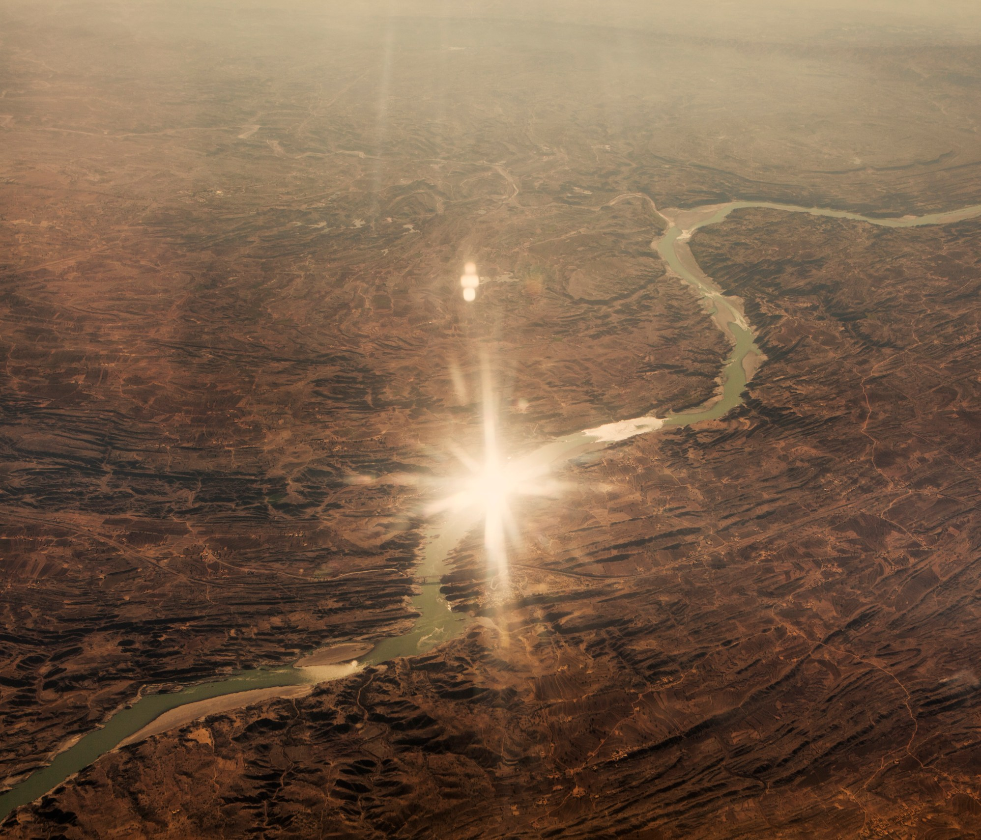An aerial view of the Helmand River sparkling with reflected sunshine. In June 2011, President Obama announced his plan to begin the withdrawal of US troops from Afghanistan, but there is currently no end date for the war in the troubled country. Helmand is the largest province in Afghanistan, and the heart of the war against terror. Commanders on the ground have described the situation as the most brutal conflict the British Army has been involved in since the Korean War. Much of the fighting between NATO and Taliban forces is taking place in this province and Helmand is a true Taliban stronghold. The Helmand River flows through the mainly desert region. With these images I am trying to show a softer side to this troubled area of Afghanistan.