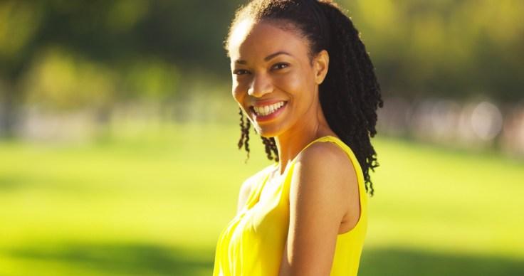 Black woman smiling in a field