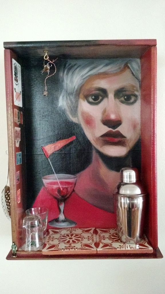photo of an original portrait painted inside a vintage drawer with talavera tile, vintage stamps, antique dental appliance and a cocktail shaker, from the series Your Bartender by Christie Mellor