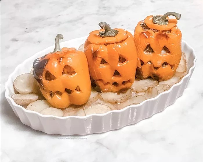 3 cooked stuffed peppers that look like jack o lanterns
