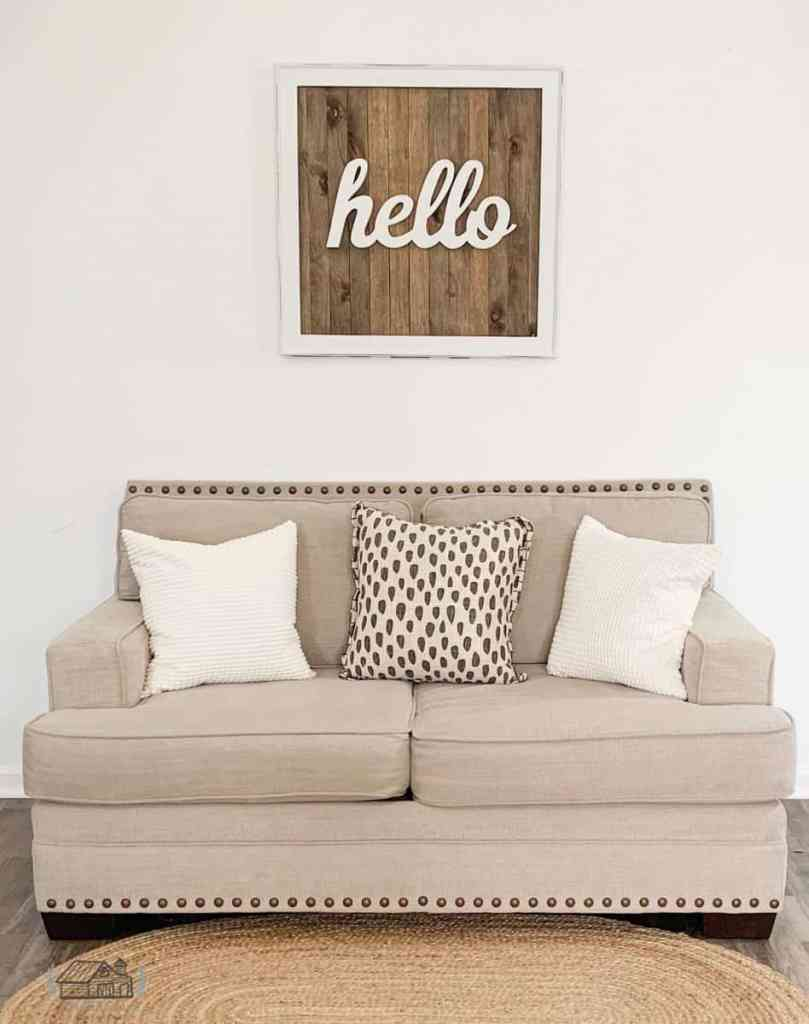 Thrift store sign hung on wall above sofa