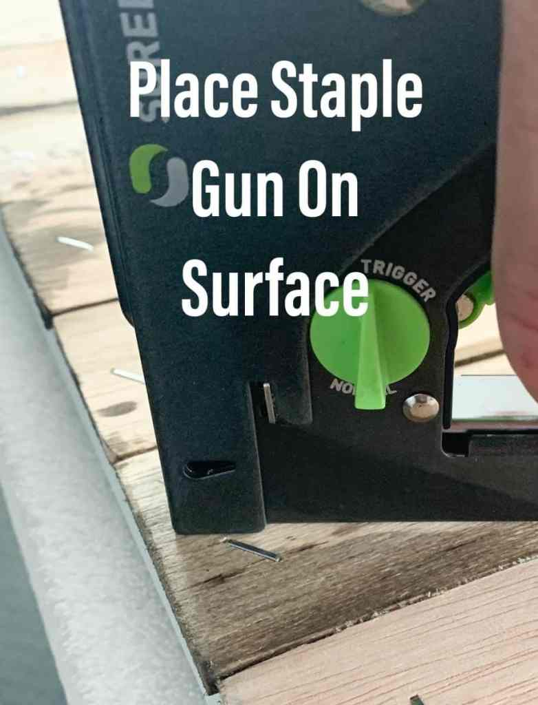Placing staple gun on surface to be stapled
