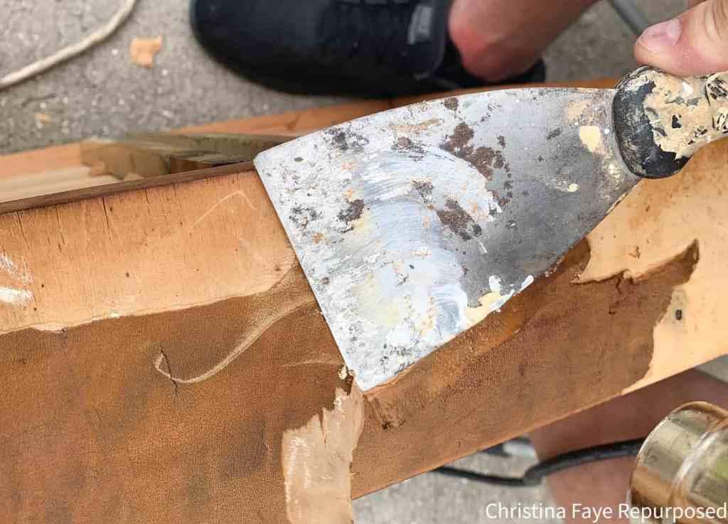 Using paint scraper to remove veneer