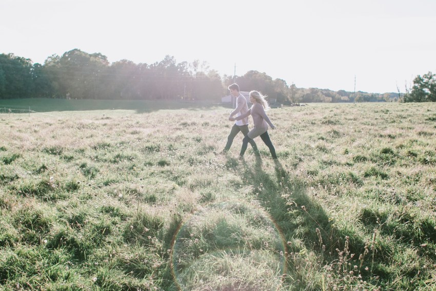A newly engaged couple walks together hand in hand through a meadow during their engagement shoot in kalamazoo, Michigan