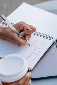 ethnic woman writing notes in notebook