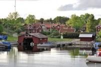 En liten by med röda hus och ett rött båthus i Stockholms skärgård. /Village in Stockholm archipelago