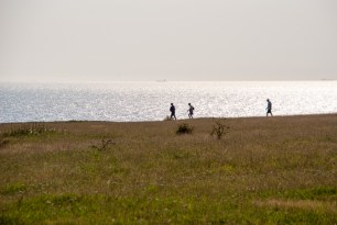 People walking along the coast and a boat passing in the distance on the sea.