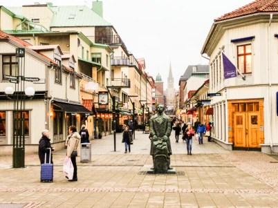 "Standing on the bridge across Viskan looking along Stora Brogatan towards one of the eastern gates. Gustav Adolfs church is seen in the distance. The statue is a ""knalle"" - a wandering salesman."