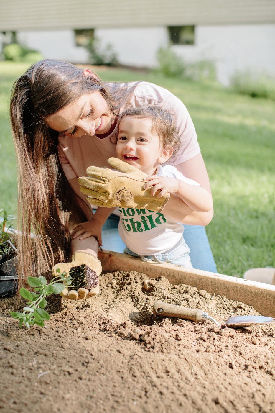mom and baby spring gardening transplanting into the garden
