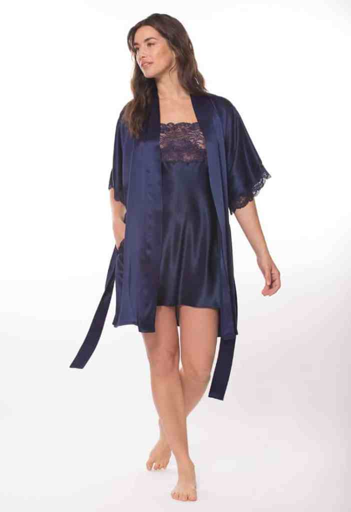 silk blue robe and chemise with lace is worn by women posed with hand in pocket looking away to the left
