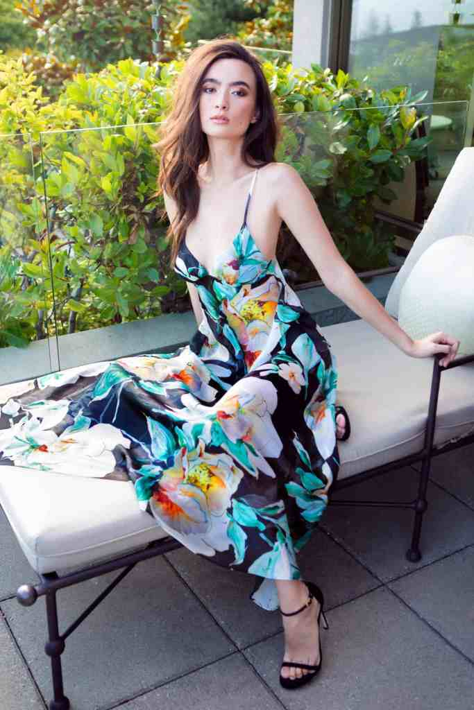 A silk gown wtih our Christine Lingerie floral Ophelia print is worn by a women sitting on a chair