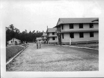 """A picture of most of our company street. The Orderly Room is on the left. The buildings on the right are barracks."""