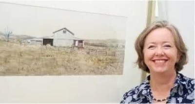 "Christine Porter, painter, in front of her woolshed watercolour ""Shed from the north"""