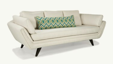 blue and green long accent pillow on cream sofa