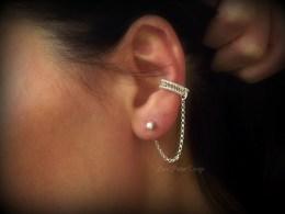Silver ear cuff on girl's ear.
