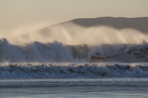 Very high winds coming from shore, blowing the wave crests back.