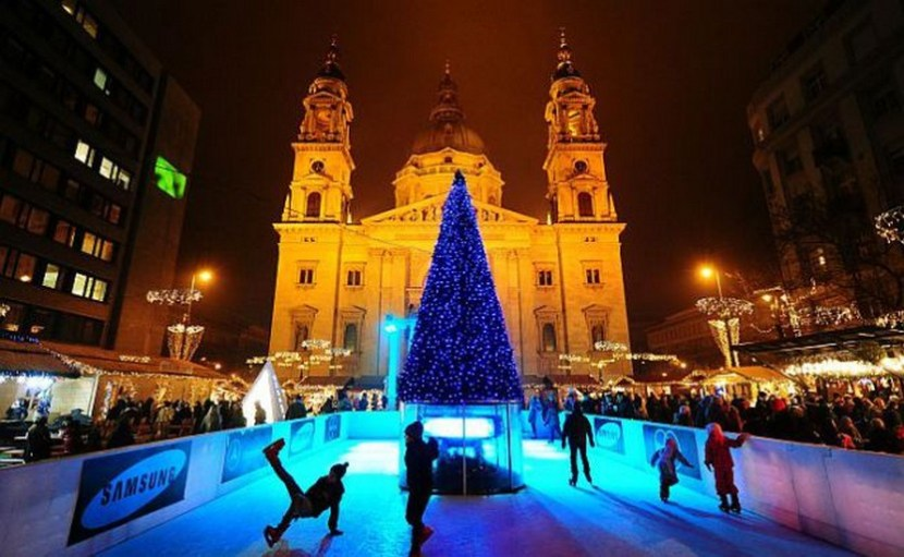 Children skate on am ice rink around a Christmas tree at a Christmas market in front of the St Stephan Basilica in Budapest – photo by Attila Kisbenedek