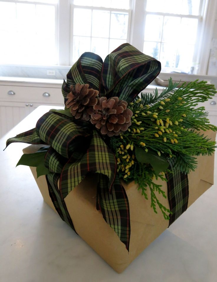 Gorgeous Christmas gift wrap design using brown paper, plaid ribbon, greenery and pinecones