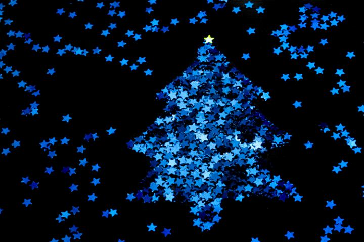 Christmas star tree made from a myriad of tiny blue stars on a black background
