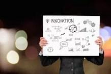 anager hält Schild mit Innovation hoch