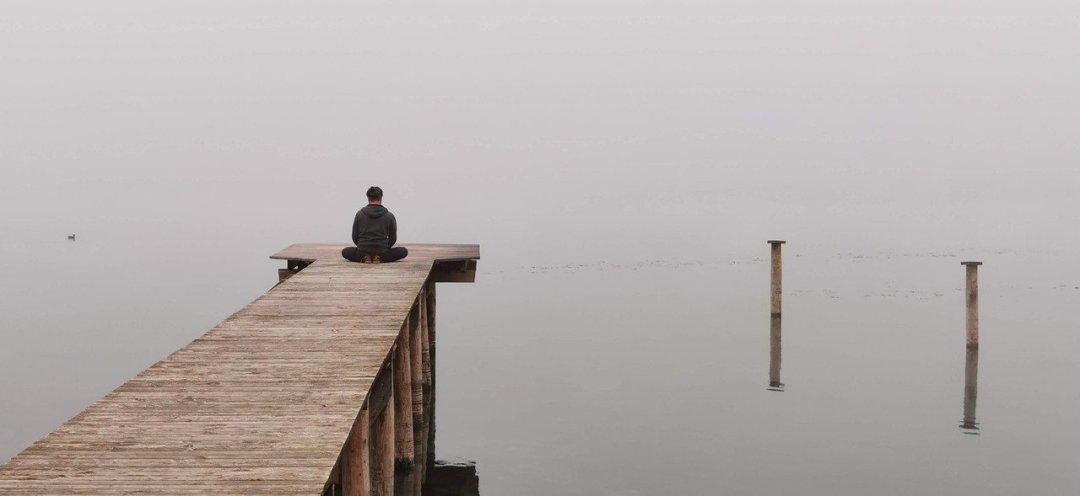 homme meditant au bout d'un ponton