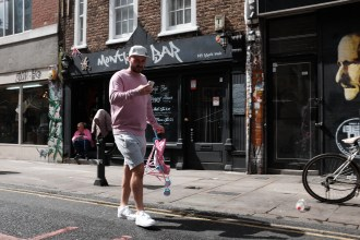 Pink man in shoreditch on phone with pink pram