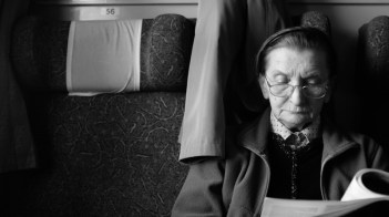 woman reading on train in black and white