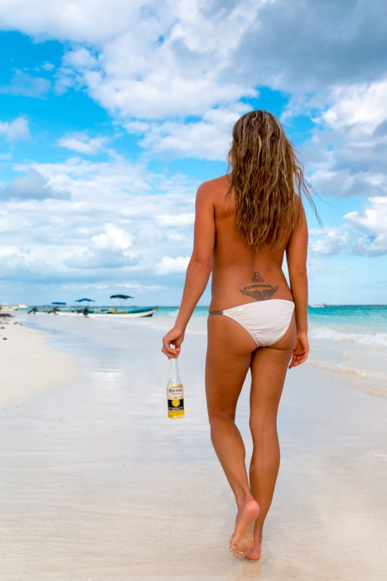 Corky from behind, topless in a white bikini bottom, holding a Corona bottle as she walks down the beach in Tulum, Mexico. Photo by Christopher Keelty.