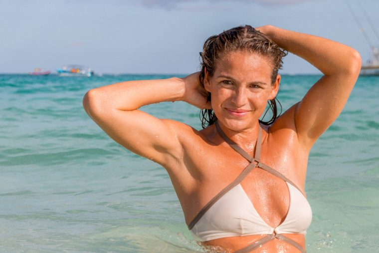 Corky in the ocean in Tulum, Mexico, wearing a white and brown bikini top. Photo by Christopher Keelty.