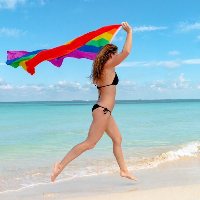 Model Corky, in a black bikini, runs down the beach with a rainbow gay pride flag. Photo by Christopher Keelty.